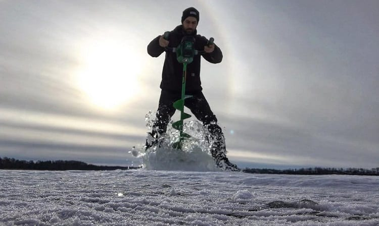 Man Drilling Ice For Ice Fishing