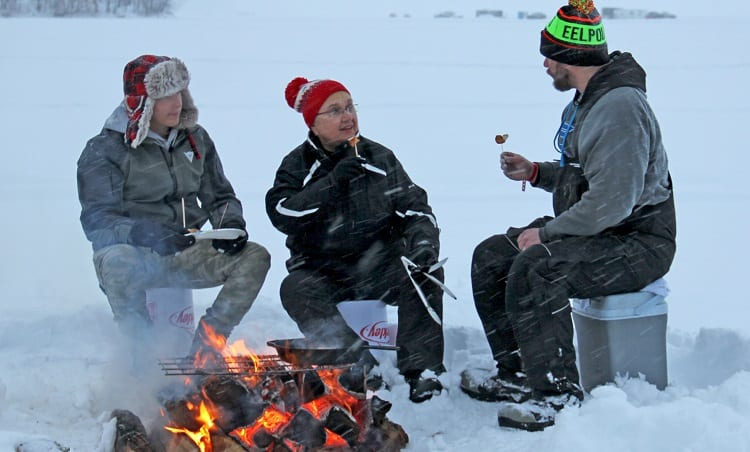 Group Of Man Eating On Ice Fishing